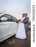 bride and groom near a car in a ... | Shutterstock . vector #739335025