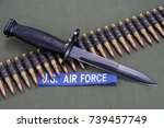 Small photo of bayonet and ammunition belt on US AIR FORCE uniform background