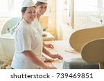 Small photo of Baker women working in bakehouse of bakery looking into camera