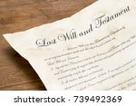 Small photo of Close up shot of an aged last will and testament on a wooden table top