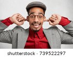 Small photo of Funny mixed race man wears cap and red shirt with jacket, plugs ears and smiles joyfully as doesn`t want to hear loud noise or noisy neighbours. Comic dark skinned male isolated over white wall