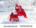 Kids sledding in winter forest. Children drink hot chocolate on sled under warm blanket. Boy and girl play in snow on Christmas vacation. Xmas family fun. Kid with cocoa on sledge. Child with sleigh.