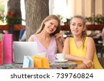 young women with laptop in cafe | Shutterstock . vector #739760824