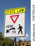 Small photo of State law - Yield here to pedestrians sign