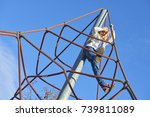 Small photo of Active young child girl climbing the spider web playground activity. Children outdoor activities.