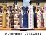 """Small photo of Summer fete """"Water and Wine"""" stall with wrapped bottles in colorful wrapping paper."""