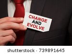 Small photo of Businessman putting a card with text Change and Evolve in the pocket