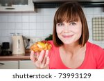 Beautiful woman holds sweet bun with fruits - stock photo