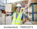Small photo of Warehouse worker holding package on the shoulder for delivery to customer.