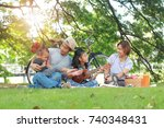 happy asian family picnic in... | Shutterstock . vector #740348431