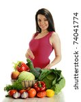 Young smiling woman standing at the table with variety of fresh raw vegetables isolated on white - stock photo