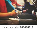 pregnant woman travel by plane | Shutterstock . vector #740498119
