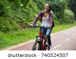 cheerful young woman cyclist... | Shutterstock . vector #740524507
