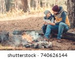 Small photo of happy father and son using digital tablet while sitting on log in autumn forest