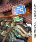 Small photo of To be renovated faded blue wooden beam with a white counterclockwise swastika meaning good fortune and reffering to Buddha's heart in Buddhism