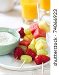 Platter of fruit skewers with a dish of yogurt.  Healthy party food, with orange juice behind. - stock photo