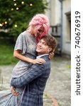 Small photo of Man holds tender woman with pink hair standing against the wind