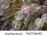 Small photo of Close up of several strands of colorful faceted watermelon fluorite beads. Focal plane is on the green bead toward the center of the image.