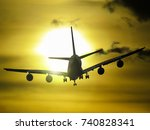 airplane flies into the sunset | Shutterstock . vector #740828341