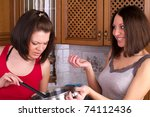 Two beautiful female trying to cook soup on the home kitchen - stock photo