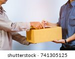 Small photo of close up of Hand man sending a cardboard box to a customer as a sign receive a parcel / parcel delivery concept