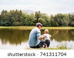 father and the son by the lake... | Shutterstock . vector #741311704