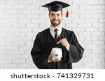Young Graduate With Piggy Bank...