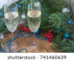 Small photo of Christmas and New Year still life composition with two champaign glasses, pine tree acerose, red rowan berries, blue and silver balls, garland ornament decoration, copy space