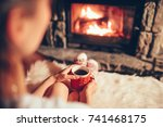 woman holding a cup of tea by... | Shutterstock . vector #741468175