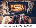 feet in woollen socks by the... | Shutterstock . vector #741468301