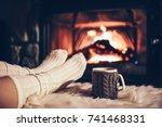 feet in woollen socks by the... | Shutterstock . vector #741468331