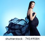 Young beautiful sexy and stylish  pregnant woman in blue - blue background - stock photo