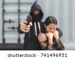 Small photo of Crime concept. Thief was threatening hostage with gun.