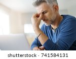 man at home having a headache... | Shutterstock . vector #741584131