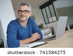middle aged man working from... | Shutterstock . vector #741584275
