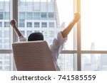 Small photo of Work achievement in business concept with happy businessman relaxing in office room, resting and raising fists with ambition looking forward to city building urban scene through glass window