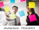 Small photo of Colorful stickers on glass panel help female designer and her associate in job