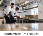 two male cooks preparing food... | Shutterstock . vector #741701821