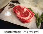 raw ribeye steak lying on kraft ... | Shutterstock . vector #741791194