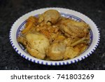 Small photo of Algerian traditional dish (Chekhchoukha )with thin semolina leaves cooked, chicken meat and vegetables in artisanal plate on black background.