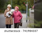 Stock photo senior woman walking her little dog on a city street with her granddaughter looking happy and 741984337