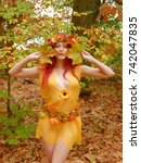 Small photo of A beautiful young woman dresses up as an Autumn forest fairy and wears a wreath head ornament made out of Autumn leaves. She poses for the camera admiring the full color scenery of fall.