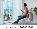 smiling asian man drinking... | Shutterstock . vector #742059781