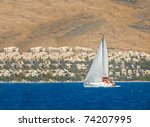 Yacht sailing in the sea near mediterranean town - stock photo