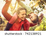 mom gives a ride on piggyback.  | Shutterstock . vector #742138921