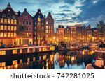 Stock photo evening town amsterdam in netherlands on bank river canal amstel with shining window panorama 742281025