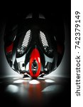 Small photo of Future technologies. Aerodynamic aggressive forms on a black background. Bicycle mountain bike safety helmet.
