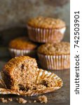 Small photo of Close up of a bran muffin with crumbs and muffins in the background.
