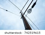 Small photo of Telephone Pole Extends Dramatically Into the Sky, Wires Extend in all Directions