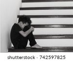 Small photo of Sad boy is sitting on the stairs, sad boy
